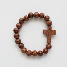 "Wooden Cross Bracelet. This 7"" wooden bead bracelet is handmade of fallen Acacia Tortilis trees by Maasai artisans in Kenya and strung on a versatile elastic. It comes in two colors - dark and blonde. The blonde turns to a warm honey color with wear. Makes a great Christmas gift and stocking stuffer!"