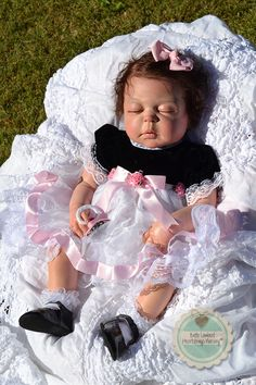 "Sleepy little SOKENZY JADE is a custom ordered baby made from Sheila Michael's 'Cameron"" sculpt. She is 23"" long and is a full body, anatomically correct little girl. She has dark brown hand-rooted mohair curls and hand-rooted lashes. Sokenzy lives in MARTINIQUE. See her at www.heartstringsnursery.com"
