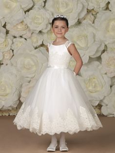 Satin and tulle off-the-shoulder tea-length dress with lace cap sleeves, satin bodice with hand-embroidered lace overlay, satin ribbon waistband and tie back sash, full tulle skirt with matching hand-embroidered scalloped lace trim. Sizes:2 – 16
