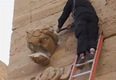 ISIS destroys historic statues at Iraq's Hatra. In this image made from a militant video posted on YouTube on Friday, April 3, 2015, which has been verified and is consistent with other AP reporting, a piece falls off from a curved face on the wall of an ancient building as a militant hammers it in Hatra, a large fortified city recognized as a UNESCO World Heritage site, 110 kilometers southwest of Mosul, Iraq [Credit: AP/Militant video]