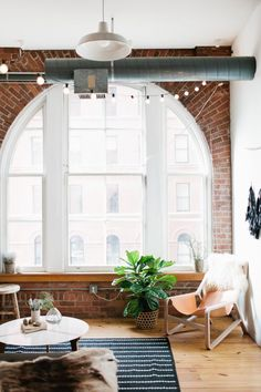 Madelynn Furlong's Minneapolis Apartment Tour | The Everygirl // loft living room // huge windows // twinkle lights // Scandinavian design // photo by Canary Grey Photography