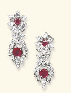 A PAIR OF RUBY AND DIAMOND EAR PENDANTS, BY VAN CLEEF & ARPELS  Each detachable pendant centering upon a cushion-cut ruby, within an articulated circular-cut diamond foliate surround, suspended by a diamond collet from a surmount of flowerhead design, set with a square-cut ruby pistil and circular-cut diamond petals, mounted in white gold, circa 1964