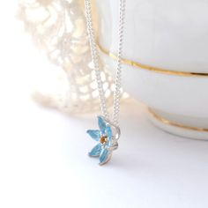 Something borrowed, something blue.... This Blue Topaz Flower Necklace would make a meaningful gift for your bridesmaids. The  vibrant blue would really stand out when paired with a corsage of blueish flowers such as love-in-the-mist, bluebells, eucalyptus leaves and sea holly.