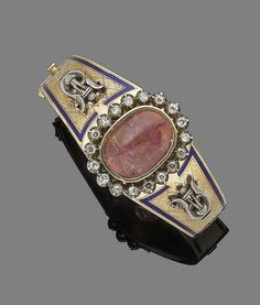 An enamel, tourmaline and diamond hinged bangle Set to the front with a large oval cabochon pink tourmaline in collet-setting, within a brilliant-cut diamond surround and to tapering shoulders highlighted with a royal blue enamel border and lyre decoration, with engraved scrolling and beading details throughout. Victorian or Victorian style.