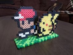Ash and Pikachu Perler bead sprites with pixel grass platform. The platform is approximately 1.5 x 4 inches and the sprites stand 2.5 inches high.