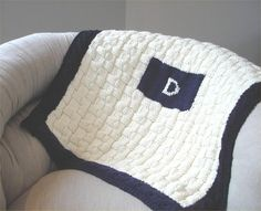 This baby blanket is the perfect keepsake gift. The main piece is knit in a basketweave pattern which is always a classic. The border is a cable that frames the entire piece. In the center we added an initial to make this blanket even more personalized. For those of you who like to get a head start on gift knitting, you can use the first or last name initial. There are so many great color cominations you can do for either a boy or girl.Materials:400 yards of main color in a chunky weight…