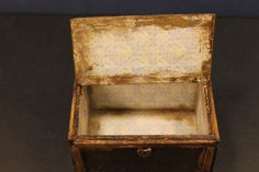 Inside the rustic wooden steamer trunk. This miniature case shows signs of wear and tear.