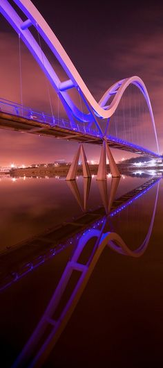 Infinity Bridge, Stockton-on-Tees, England. At night reflecting pink glow from London lights