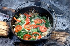 Hash browns with spinach, cheese, and tomatoes, all cooked over a campfire in a dutch oven.
