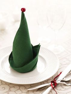 "elf hat napkin folding...fold square napkin in half with the edges away from you.  Keeping your finger at the midpoint of the fold, roll the open edges into a cone shape, using your finger to keep the point crisp. Then fold up the ""brim"" just like you would fold up a shirtsleeve. Add a bell or ball to the tip; attach it using a wire to slip down through the center of the cone."