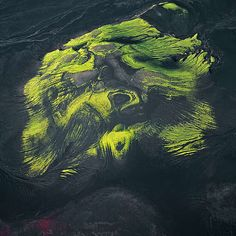 Bernhard Edmaier Aerial photography. MAELIFELLSANDER, ICELAND  Bright green moss has colonized a hill in the middle of Maelifellsandur, a black desert of lava and volcanic ash in Iceland. The hill is all what remains of a once active cinder cone, ground down by ice of the nearby retreating Maelifell glacier.