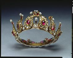 The Royal Collection: Tiara Presented to Queen Victoria and placed among Indian Collection belonging to Crown by King George V in 1924. Description: A ruby, diamond, and pearl tiara formed from twelve gold, tear-shaped sections mounted with diamonds and rubies, on a gold and pearl band, with enamel portraits at back.