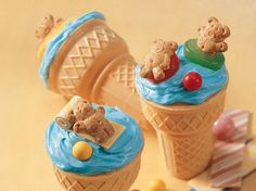"""These whimsical party cupcakes couldn't be easier to eat, or make. You bake them right in the ice cream cones, then cool, frost with the Whipped frosting of your choice, and top with whatever candies you like! We went with a teddy bear beach party theme, complete with blue frosting """"water,"""" gummy-candy """"inner tubes,"""" gumball """"beach balls"""" and striped gum """"floaties."""""""
