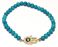 This turquoise beaded gold over sterling silver hamsa stretch bracelet features multiple faceted turquoise beads accented by a sparkling  CZ hamsa charm with a
