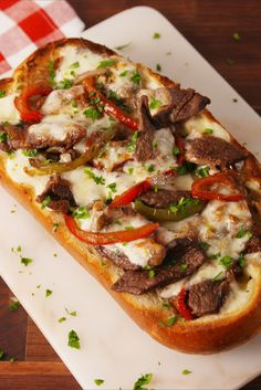 2 tbsp. vegetable oil 1 large yellow onion, sliced into half moons 2 bell peppers, thinly sliced kosher salt Freshly ground black pepper 2 lb. sirloin steak 1 tsp. oregano 12 slices provolone 1 large shallow loaf of bread, sliced in half 1 tbsp. Parsley