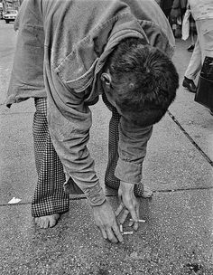 A homeless man bent over, arranging cigarette butts  in New York's Times Square.