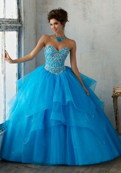 Morilee Quinceanera Dresses STYLE NUMBER: 89128 Jeweled Beading on a Flounced Tulle Ballgown Glamorous Organza Quinceañera Dress with Delicately Beaded Cascading Tiered Skirt. Sweetheart Neckline Bodice Features Intricate Jewel Beading and Corset Back. Matching Bolero Jacket Included. Colors Available: Peacock, Black Cherry, Pucker Up Pink, White.