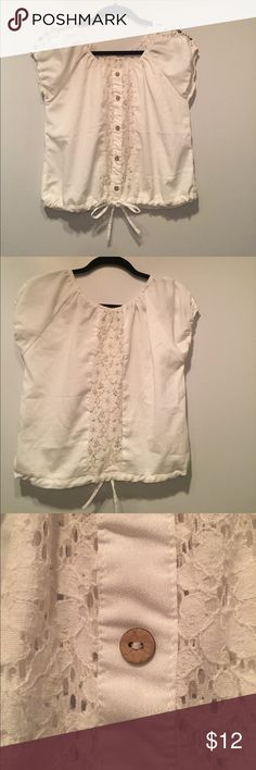 Free People White Blouse with Lace Worn Once Free People White blouse with lace and tan wooden buttons. The lace is in the front and back. The sleeves are elastic and the bottom of the blouse can be tightened by pulling the string that makes the bow. The blouse has only been worn once but the tag in the back of the shirt was carefully removed with a seam ripper because it was scratchy and I have sensitive skin. Material is high quality. The blouse is like new and is in perfect condition…