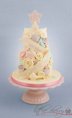 Little Cherry Cake Company (T-Cakes)  Disney Princess Cake!  Aurora's crown, Ariels shell, Cinderellas shoe, Snow Whites apple, Belle's rose, Jasmines Lamp, Rapunzel's Lantern, and Meridas arrow xxx  Strawberry cake and covered in white choc x