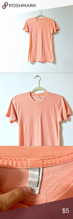 "American Apparel / Vtg Tee Peachy-orange short sleeve tee. ""Vintage"" AA, bought it thrift around 10 years ago, so I assume it's from the early- mid 00's. Has that vintage tee look and feel: soft, faded, and some pills. One tiny spot on front is pictured & was there when I got it, and there's some slight discoloration under arms. The fit and fabric make it feel like a cross between an athletic and fitted tee. Very comfy staple in a cute color. American Apparel Tops Tees - Short Sleeve"