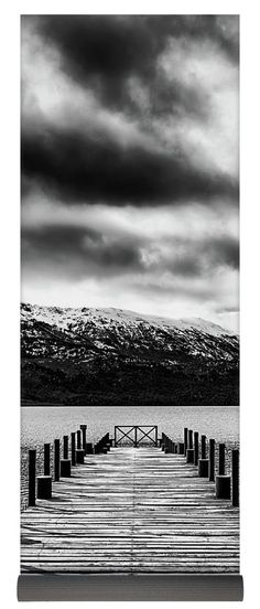 Landscape Yoga Mat featuring a black and white conversion of a photo of a dock whose lines point towards a beautiful landscape with snowy mountains under a dramatic cloudy sky in San Carlos de Bariloche, Río Negro, Argentina. Made from environmentally friendly eco-PVC. Black carrying bag with a black shoulder strap included. Worldwide shipping within 2-3 business days. Click through the image to get yours! Art for your life by Eduardo Jose Accorinti.