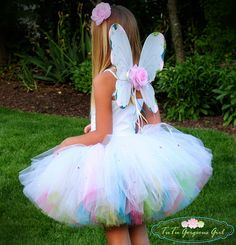The layered tutu is made with a top layer of solid white tulle. The bottom layer is made with yellow, turquoise, lime green and bubble gum pink tulle.