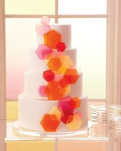 A watercolor-inspired wedding cake: White fondant topped with clusters of hard-candy hexagons