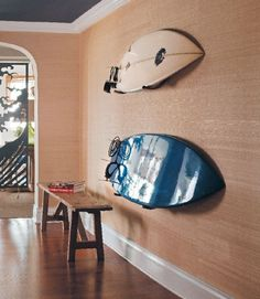 grasscloth + wood bench + surf boards in hallway entry by Philip Gorrivan via Connecticut Cottages & Gardens