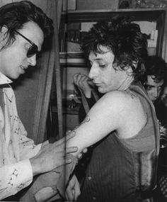 Richard Hell & Johnny Thunders - the guy in the background is Gary Green.  My college photography class was taught by him. I was taking photos of bands and he mentioned he used to take photos of bands in NYC. I brought in a book that happened to have this photo in it, and he flipped. The next week he dug out the photo he'd taken from the opposite side. Totally cool! He's got all kinds of cool photos never published before.