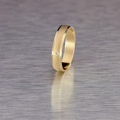 Anillo de diamantes y oro amarillo de 18k Argyor. Es una alianza de boda creada sobre la base de un diseño que combina texturas: mate para la banda central y brillo para los cantos biselados. El diamante es de talla brillante y 0,01 quilates.