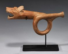 North Coast Peru, ca. 300-500 CE.  Large orange-brown glazed terracotta trumpet with cream-colored highlights depicting a ferocious, open-mouth jaguar head with large fangs.