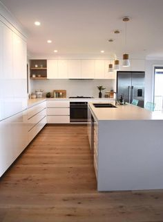 All white and light wood kitchen with small matching pendants over the island