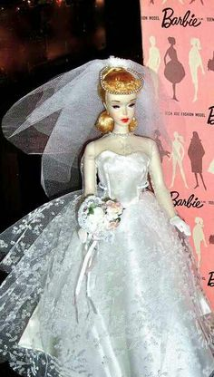 Vintage Barbie Wedding Day Set #972 (1959-1962)Bridal GownVeil with PearlsBlue GarterGraduated Pearl NecklaceShort White GlovesBouquetWhite Open Toe HeelsA beautiful bridal gown in pure white satin with an overlay of flocked and silver glitter accented tulle. The exquisitely crafted gown features a full double tier skirt with a train.