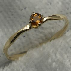 November's birthstone is the golden yellow-brown colors of amber or honey. The gem stones usually used are Topaz and Citrine. This elegant little hand crafted 14k yellow gold baby ring is set with a natural Citrine. The Citrine measures 2mm, weighs about .03 carats, and is completely natural.