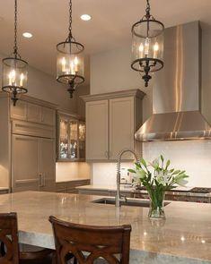 placards cuisine taupe et magnifique îlot de cuisine avec un plan de travail en marbre, suspensions vintage