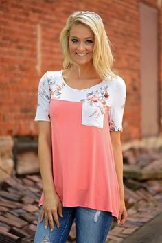A cute Coral body with ivory floral shoulders and pocket. True to size with a looser fit. 95% Rayon 5%...