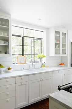 love the white glass front cabinets with the black metal industrial windows - Barbara Bestor-designed white kitchen cabinets, Remodelista Clean Kitchen Cabinets, Kitchen Reno, Kitchen And Bath, New Kitchen, Kitchen Dining, Kitchen Remodel, Kitchen Cupboard, Cupboards, New England Kitchen