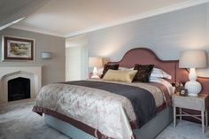 The master bedroom features soft blue silk walls and a silver faux silk carpet for ultimate luxury.The headboard creates a contrast to the 600-thread count crisp linen for the beds all layered in the satin patterned bedspread and charcoal checked throws.The pinewood bedside tables both consist of large cream lampshades, uniquely patterned bedside tables.  #bedroom #bedroomideas #bedroomdesigns #bedsidetable #wallart #lampshades #cushions #bedding
