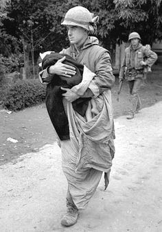 Hue, South Vietnam, February, 1968: A U.S. Marine carries a wounded Vietnamese child, wrapped in a blanket, to an ambulance for evacuation from the war-torn city. U.S. troops had been fighting to capture Hue's old Imperial Palace, a communist stronghold, for more than two weeks.