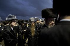 Ultra-Orthodox Jews - wearing plastic coatings on their hats - gather in the men's section...