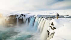 A hiker explores the stunning Godafoss waterfall, located off a beaten path in north-central Iceland at the beginning of the Sprengisandur highland road.