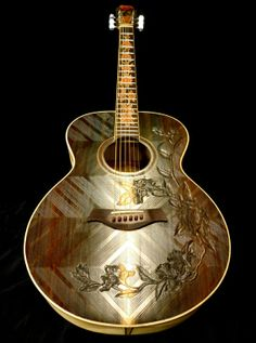 """A gorgeous rosewood-top """"Floral"""" motif grand concert guitar. Features wood inlays on the fretboard and hand carvings on the top/headstock. Sides and back are made from Balinese Angelwood. The entire body is grooved for enhancing the resonance and appearance of the instrument."""