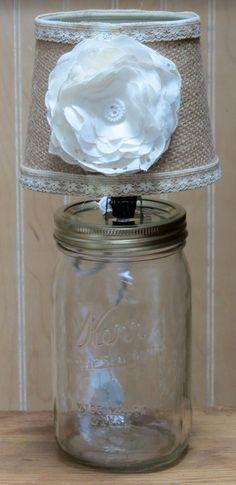 The burlap lamp shade is decorated with cream colored lace and a muslin flower secured with a button.  A lamp conversion kit helped me set this up with a quart mason jar.
