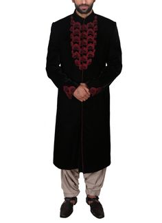 A smart achkan by Poonam Kasera that reflects a style that is reminiscent of royalty. The lush black velvet achkan is adorned with appliqué of maroon bootis with Aari embroidery on them. If you want to wear something traditional other than the kurta-pyjama, this achkan paired with a contrasting white churidar pyjama is an excellent option.