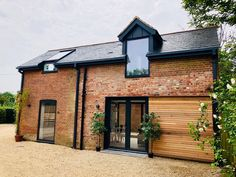Modern Coach House / Barn Conversion and renovation project by LA Hally Architect, including contemporary elements of cedar cladding, an aluminium canopy & window frame, dark grey aluminium windows, and contemporary up & down lighters.