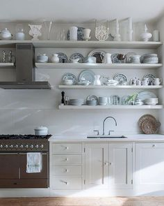 A collection of porcelain, glass and textiles is central to the design of garden designer Lorraine Johnson's mid-Victorian London home. Her collection of blue & white china and decorative vases brings a traditional contrast to the contemporary kitchen fittings. #kitchen #kitchendesign #interior Photograph Jody Stewart