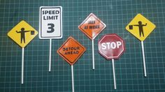 Construction sign props for a birthday cake. Detour, Flag Men, Speed Limit, and Stop Sign. Cut out with my Silhouette Cameo, Modge Podged together with cake pop sticks stuck between the front and back pieces.