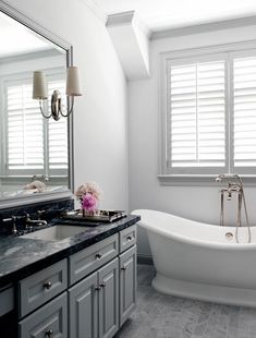 source: Courtney Hill Interiors    Gray bathroom with freestanding tub, polished nickel floor mount tub filler, gray paint color, marble tiles floor, gray bathroom cabinet with black marble countertop and gray framed bathroom mirror. decorpad.com
