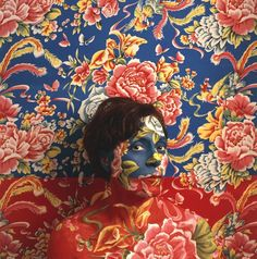 "Interdisciplinary artist Cecilia Paredes practices what she calls ""photoperformance,"" using body paint and other materials to camouflage herself in elaborate, decorative environments. The result is documented in photographs that resemble paintings because, in part, they are. For her ""Landscape"" series, Paredes chooses elaborate, floral patterns, creating an interesting juxtaposition between the natural and the artificial."