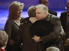 Garth Brooks, right, hugs Larry Gatlin as Brooks and Trisha Yearwood, left, arrive for the funeral for country music star George Jones in the Grand Ole Opry House (2013)